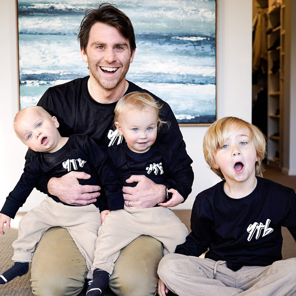 jimmy and his three boys wearing matching lack shirts with YTB logos on them, slang for yeah the boys